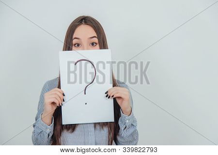 Inquisitive Asian Student Girl Hiding Her Mouth Behind A Sheet Of Paper With Question Mark Written O