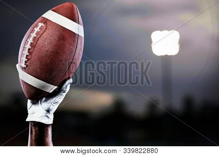 Hand of a player holding American football against close-up of soccer field