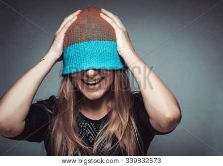 Portrait of a cheerful smiling female student wearing a hat on her face, playing and having fun, concept of enjoying life, funky youth, street urban style fashion for youngsters