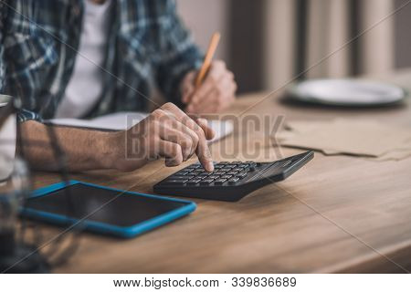 Man Using A Calc And Other Gadgets For Financial Estimation