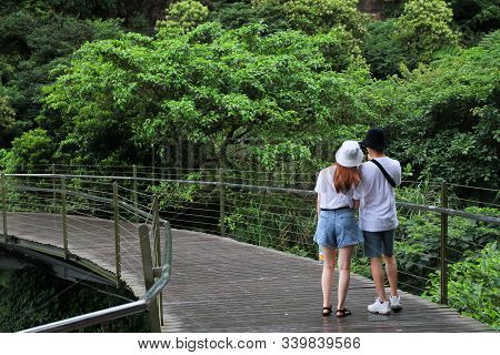 Picture Of Young Couple Wearing White T-shirt Are Standing On Wooden Bridge Walkway. Jiufen-jinguash