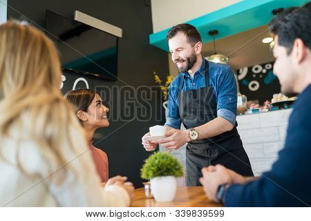 Smiling Waiter Serving Coffee To Young Customers At Restaurant