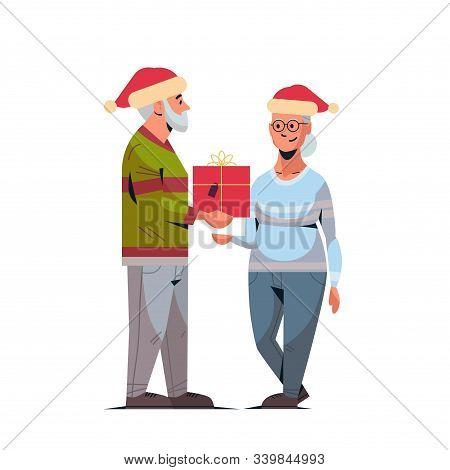 Senior Man In Santa Hat Giving Present Gift Box To Mature Woman Family Celebrating Merry Christmas H
