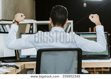 Back View Of Bi-racial Trader Showing Yes Gesture And Sitting At Table