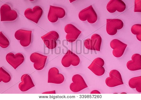 Valentine's day many red silk hearts on pink paper background, love concept