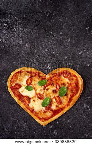 Homemade Heart Shaped Vegetarian Pizza On Black Background