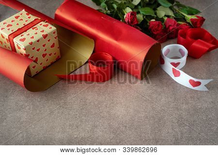 Gift Box Wrapped In Red Paper, Roses And Wrapping Materials On Brown Background