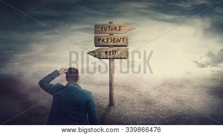 Surreal Scene, Businessman And A Signpost Arrows Showing Three Different Options, Past, Present And