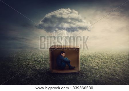 Surreal Concept With A Scared Guy Shelters Inside A Cardboard Box. Introvert Man Caged By Own Fears