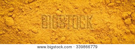 Turmeric root powder background and texture, panoramic banner