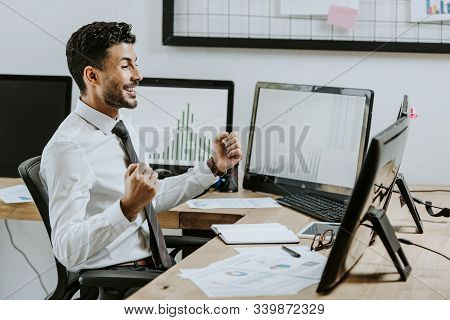 Side View Of Smiling Bi-racial Trader Showing Yes Gesture And Looking At Computer