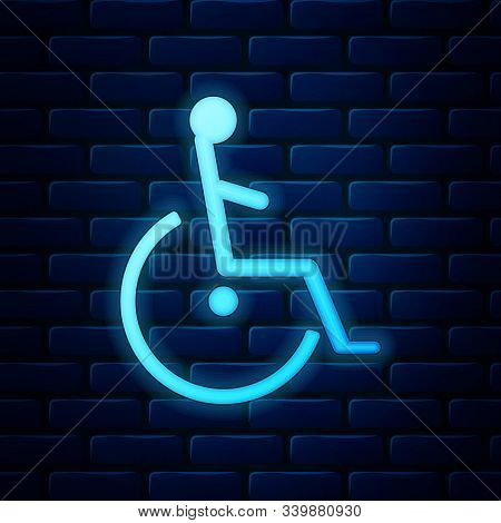 Glowing Neon Disabled Handicap Icon Isolated On Brick Wall Background. Wheelchair Handicap Sign. Vec