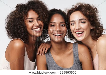 Portrait of three young multiracial women standing together and smiling at camera isolated over white background