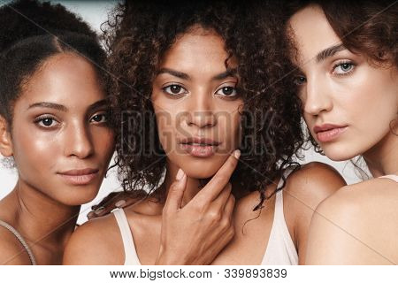 Close up beauty portrait of three attractive young sensual multiethnic women looking at camera isolated over white background