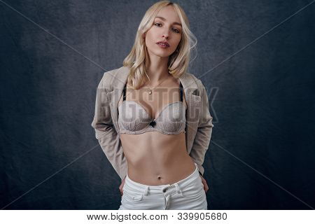 Attractive Young Blond Woman With Opened Blazer Showing Her New Bra And Giving The Camera A Sultry L