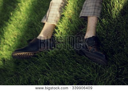 Man Lying And Relaxing On The Grass. Legs, Top View.  Pair Of Male Legs In Shoes Lying On Green Gras
