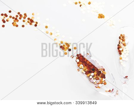 Two Transparent Wine Glass With Golden Spangles. Festive Copy Space With Crockery On White Backgroun