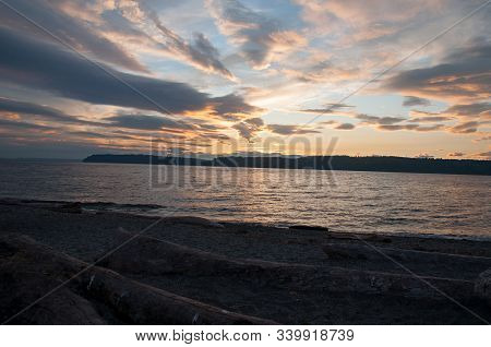 Beach Sunset Mulkiteo Washington Landscape With Sand And Lots Of Driftwood Against Bright Evening Sk