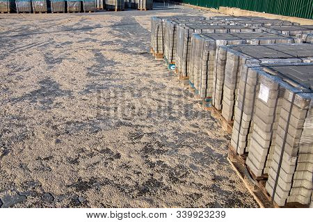 Pallets With New Paving Slabs In The Area Paved With Stone Tiles Strewn With Sand For Grouting.