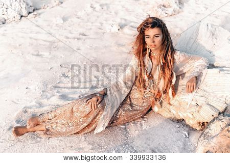 Beautiful Young Woman In Elegant Dress Lying On Sand At The Beach At Sunset