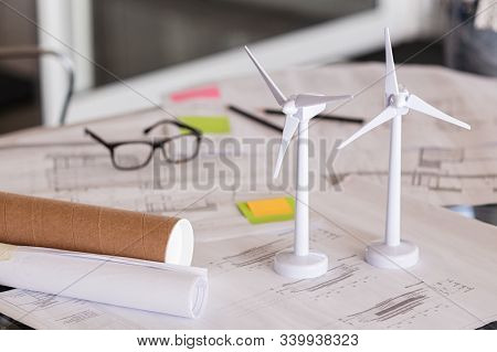 Close up of wind turbines on a table with architectural plan blueprints. Two models of wind turbines on desk with architecture layout and paper. Green and eco sustainable architecture.