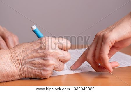 Elderly Woman Signs A Paper Document. Signing Papers. An Elderly Man Signs A Document. Woman Of Reti