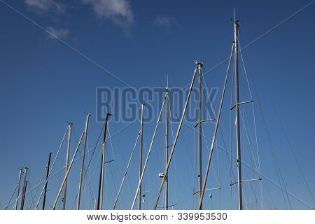 Line Of Sailboat Masts Against Blue Sky