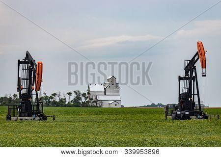 Pair Of Oil Wells Flank Grain Elevator On Prairie