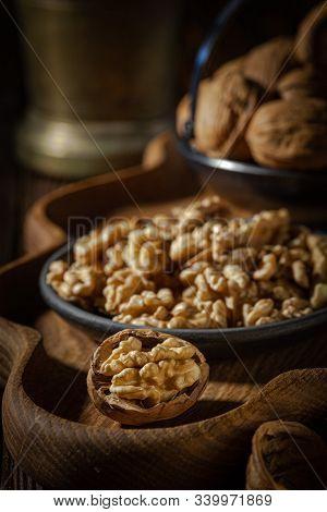 Walnuts, Decorticated Walnuts And Walnut Shells On Wooden Background