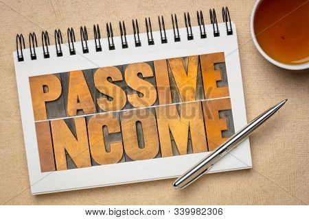 passive income word abstract in letterpress wood type in an art sketchbook with a cup of tea  - business financial flat lay concept