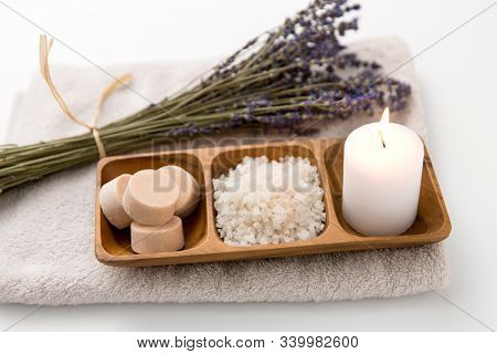 beauty and wellness concept - sea salt, soap and candle on wooden tray and bunch of lavender on bath towel