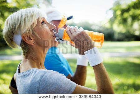 Mature Couple Drinks Water To Replenish Energy And To Hydrate