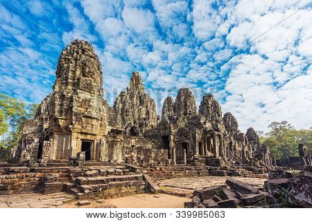Bayon Temple With Cloud, Blue Sky And Tourist In Angkor Wat Angkor Thom Area, Siem Reap Of Cambodia.