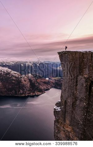 Man Hiker Standing On The Famous Preikestolen Pulpit Rock Over The Lysefjord, Some Snow On The Peaks