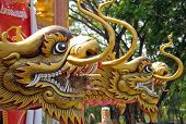 Dragon heads at Chinese temple. Notice the bird's nest in the first dragon's mouth. poster