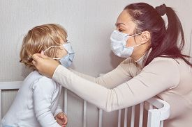 Adult White Caucasian Woman With Medical Mask On Her Face Is Putting The Same Mask On Her Little Dau