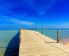 Wooden Empty Terrace Dock Or Pier. Wooden Dock Pier Blue Sea & Sky Background. View Of Wooden Dock I