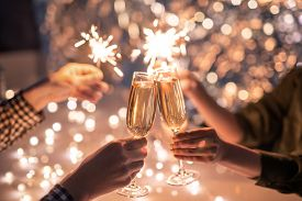 Hands of couple clinking with flutes of champagne and their friends holding sparkling bengal lights