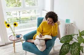 Portrait Of A Beautiful Mixed Race Woman Sitting In An Armchair, Relaxing At Home, Drinking Tea And