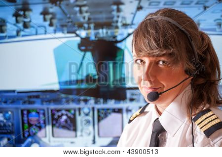 Beautiful woman pilot wearing uniform with epauletes, headset sitting inside airliner with visible cockpit during flight. poster