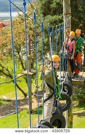 Young friends having fun in adventure park in helmets