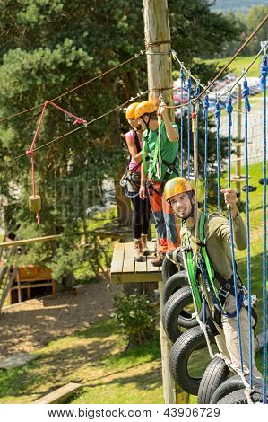 Adventure park visitors climbing on rope ladder adrenalin leisure time