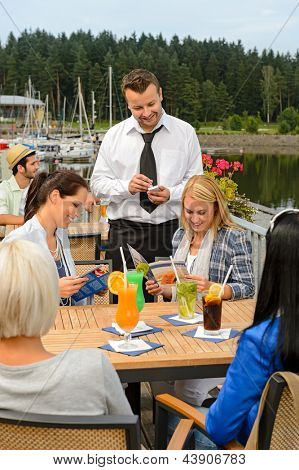 Waiter taking orders at sidewalk bar from young women