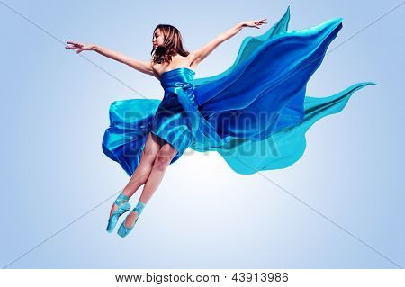 Beautiful ballet dancer with flowing blue fabric dancing with grace in studio