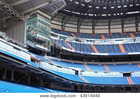 Rows of blue seats for fans at empty large football stadium. poster