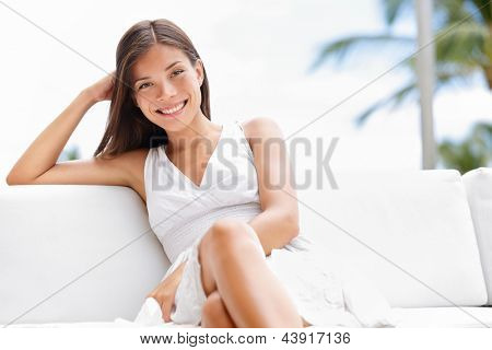 Portrait of young happy confident asian woman sitting outside in sofa smiling at camera with professional self assured confidence. Beautiful multicultural woman in luxury setting outside.