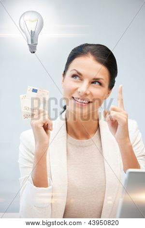 happy woman with cash euro money and light bulb