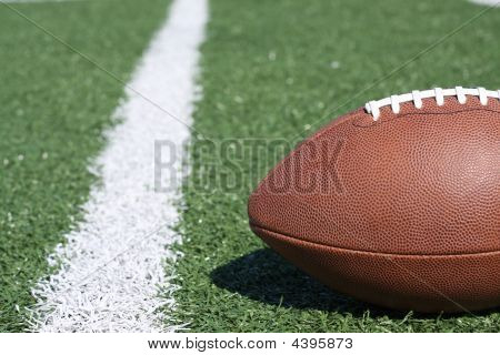 An American football laying near the yardline poster