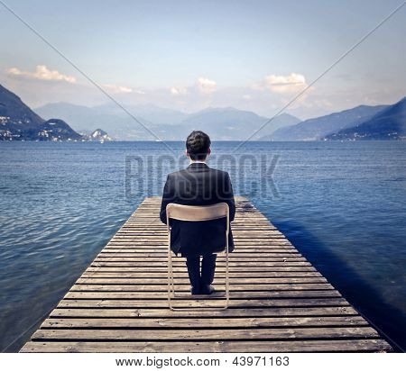 young businessman sitting on a chair looks the lake