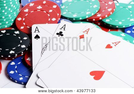 Four ases and casino chips close up